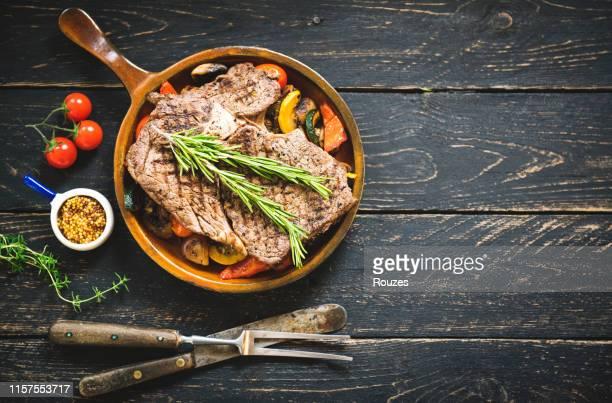 bife de carne grelhado no fundo de madeira escuro da tabela, vista superior - table top - fotografias e filmes do acervo