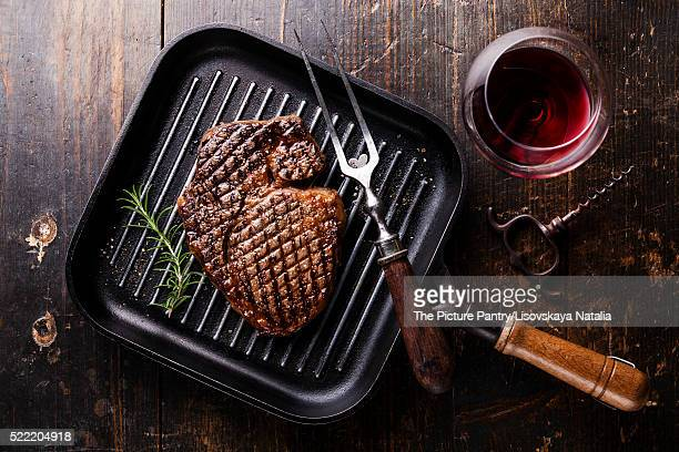 Grilled Black Angus Steak Ribeye on grill iron pan on wooden background with wine
