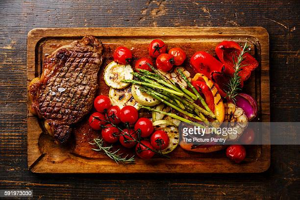 Grilled Black Angus Steak Striploin and vegetables on cutting board on wooden background