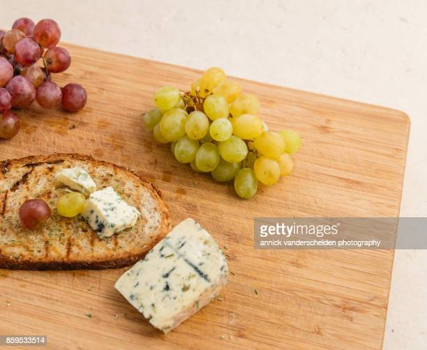 grilled bread with olive oil, grapes and blue d'auvergne. - auvergne stock pictures, royalty-free photos & images