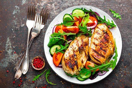 Grilled chicken breast. Fried chicken fillet and fresh vegetable salad of tomatoes, cucumbers and arugula leaves. Chicken meat with salad. Healthy food. Flat lay. Top view. Dark background 928823336