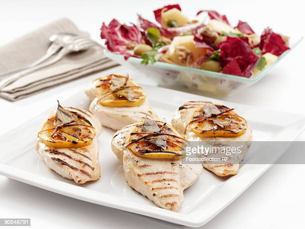 Grilled chicken breasts with slices of lemon and salad, close up