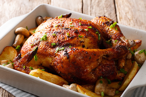 grilled chicken with mushrooms and potatoes close-up in a baking dish. horizontal 1044330750