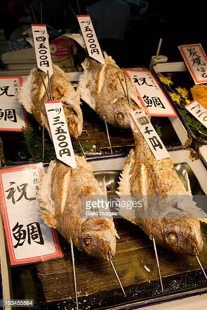 grilled fish on display at food stall at nishiki ichiba market, kyoto, honshu island, japan - nishiki market stock photos and pictures