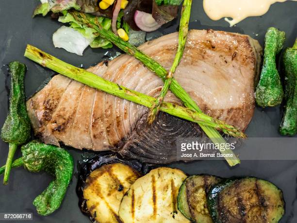 Grilled Fished tuna served on a plate of slate with  roast vegetables, peppers, asparagus and aubergine.