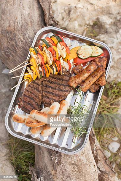 grilled food in aluminium dish on tree trunk, close up - vegetable kebab stock pictures, royalty-free photos & images