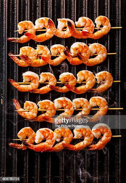 grilled fried prawns on skewers on black cast iron grill background - metal grate stock photos and pictures