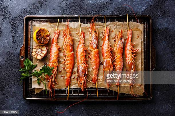 Grilled fried prawns shrimps Langostino Austral on skewers on metal grid baking sheet on black background