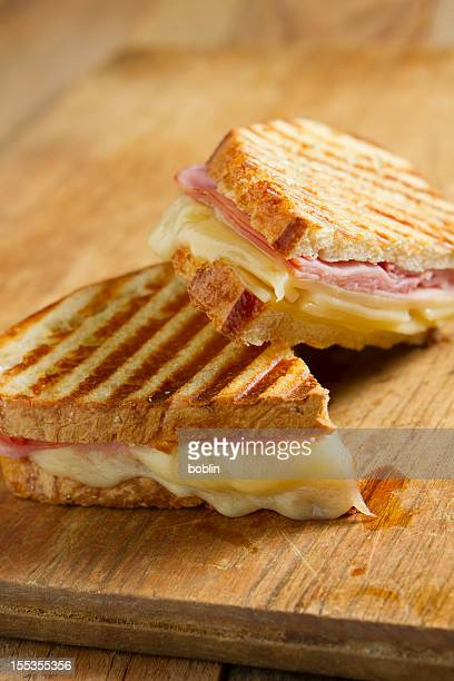 Grilled ham and cheese panini sandwich on wood table