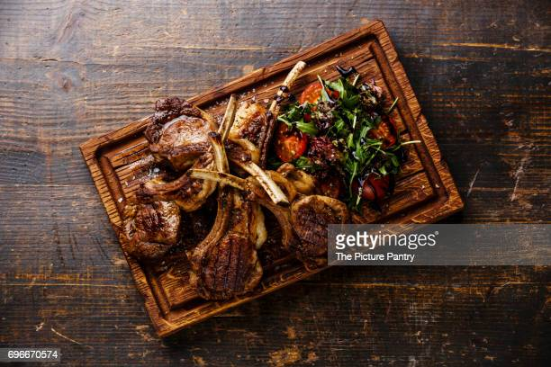Grilled lamb ribs with arugula and tomatoes on cutting board on wooden background