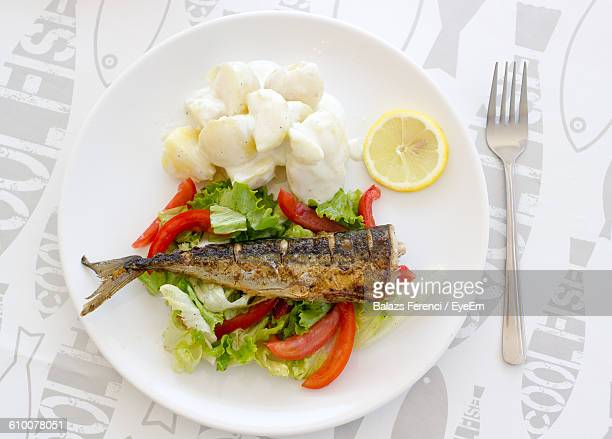 Grilled Mackerel On Salad By Potatoes Served In Plate On Table