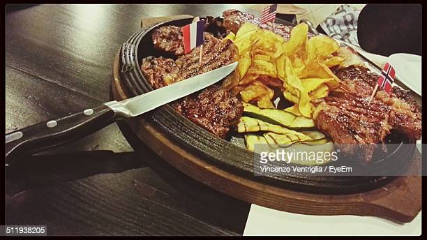 Grilled meat and potato chips served in wooden pot