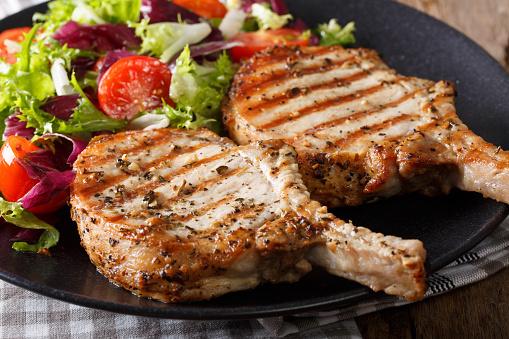 Grilled pork steak with bone and fresh salad close-up. horizontal 982391002