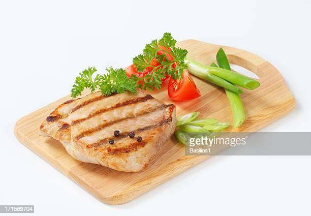 grilled pork steak with vegetable garnish on a cutting board