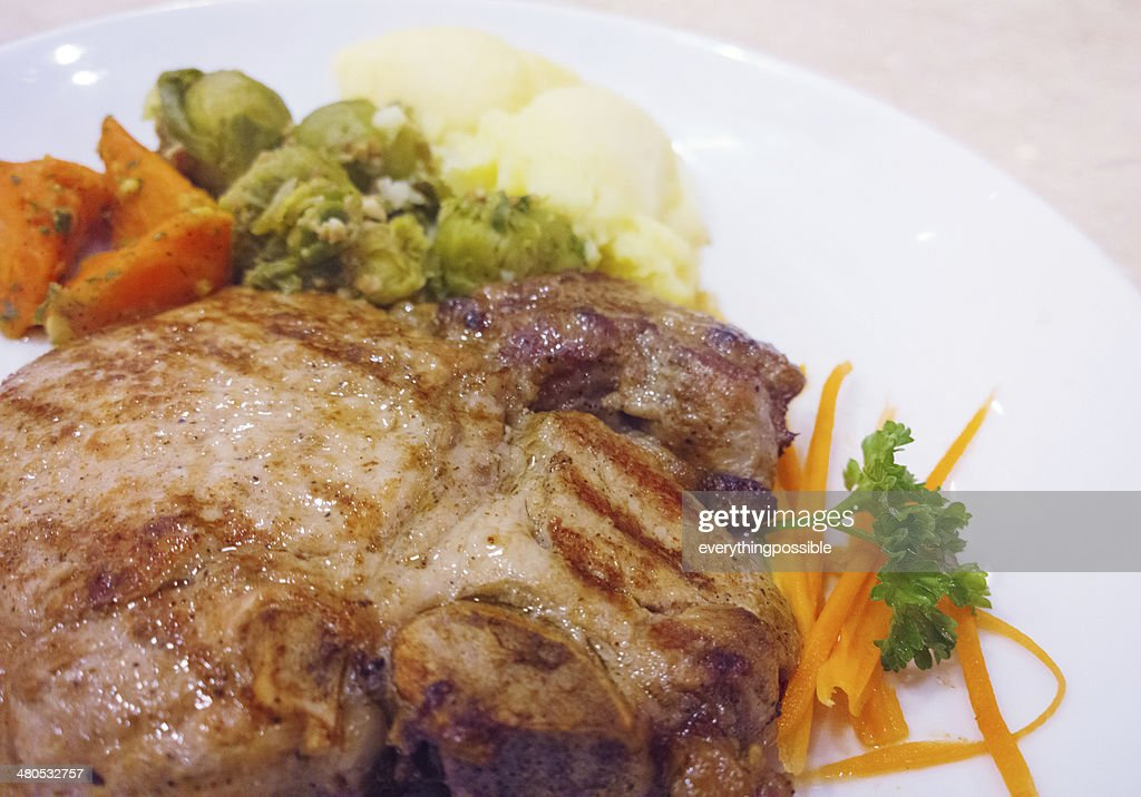 Grilled pork steaks baked potatoes and vegetable salad : Stock Photo