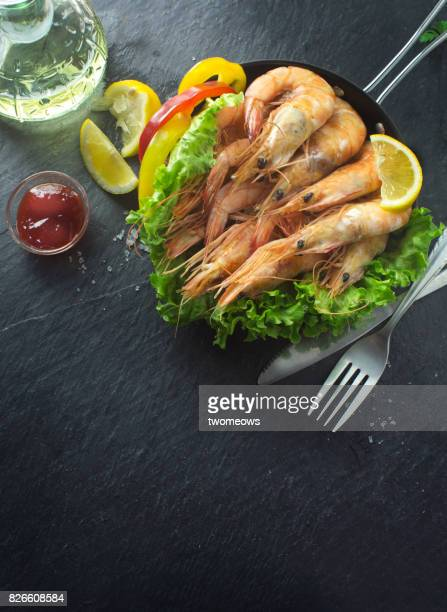 Grilled prawn and vegetables in frying pan on moody background.