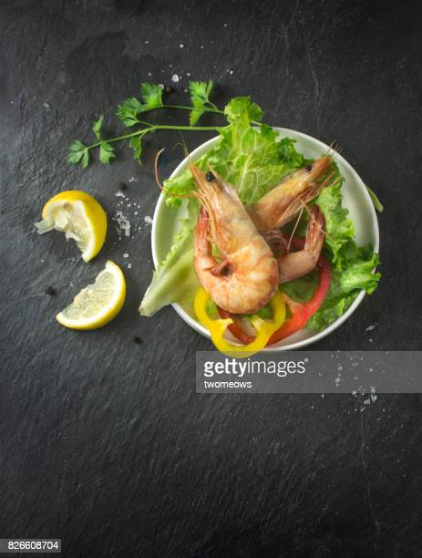 Grilled prawn and vegetables in plate on moody background.
