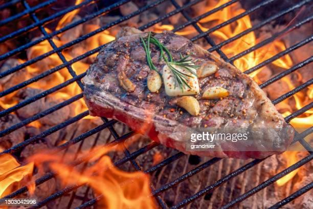 bifteck de ribeye grillé sur un gril chaud de charbon de bois avec des flammes garnies des gousses d'ail sautées une patotée de beurre et de romarin - aliment grillé au charbon de bois photos et images de collection