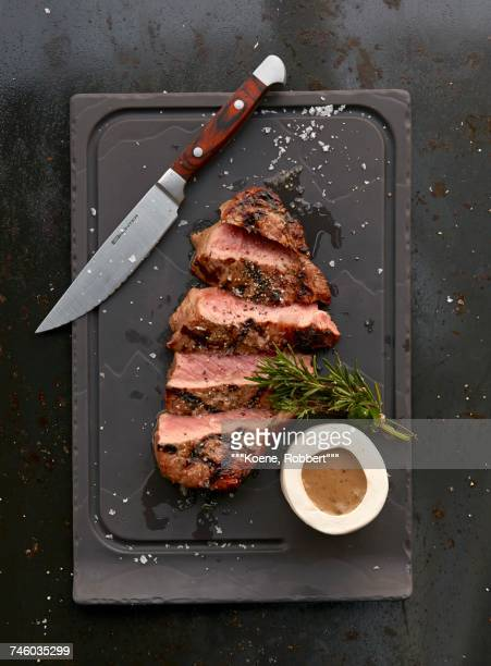 A grilled ribeye steak with sauce