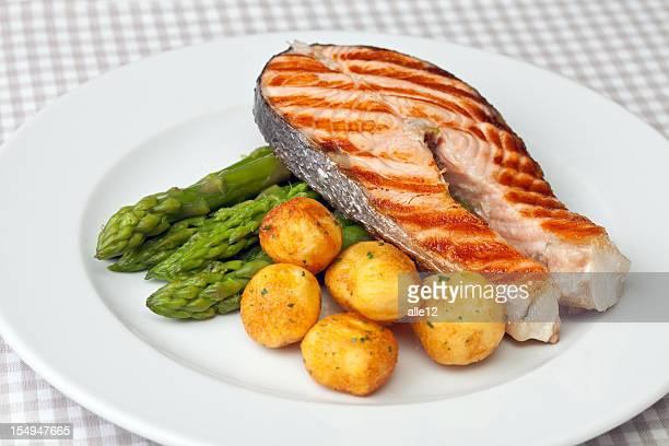 Chuleta de salmón a la parrilla con espárragos y papas.