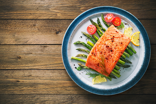 Grilled salmon garnished with green asparagus and tomatoes 935316790