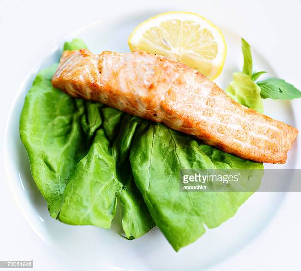 grilled salmon on green salad leaf with lemon - lemon leaf stock photos and pictures