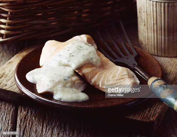 grilled salmon with white sauce on vintage plate - bechamel sauce stock photos and pictures