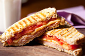 Grilled sandwich sliced in half in wooden table