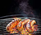 Grilled sausages on grill with smoke and flame