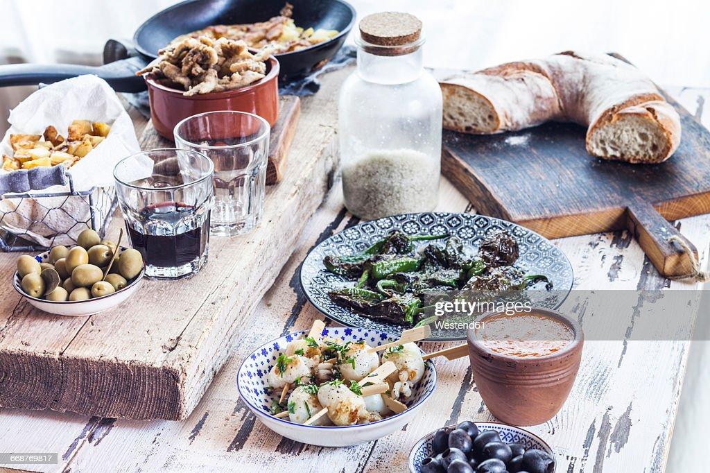 Grilled sepia, olives, pimientos de padron , Mojo sauce, patatas bravas, tortilla de patate, boquerones fritos, vino and bread : Stock Photo