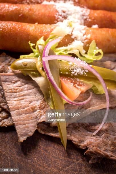 Gegrillte Scheiben vom Steak und mexikanische Enchiladas (Cecina)