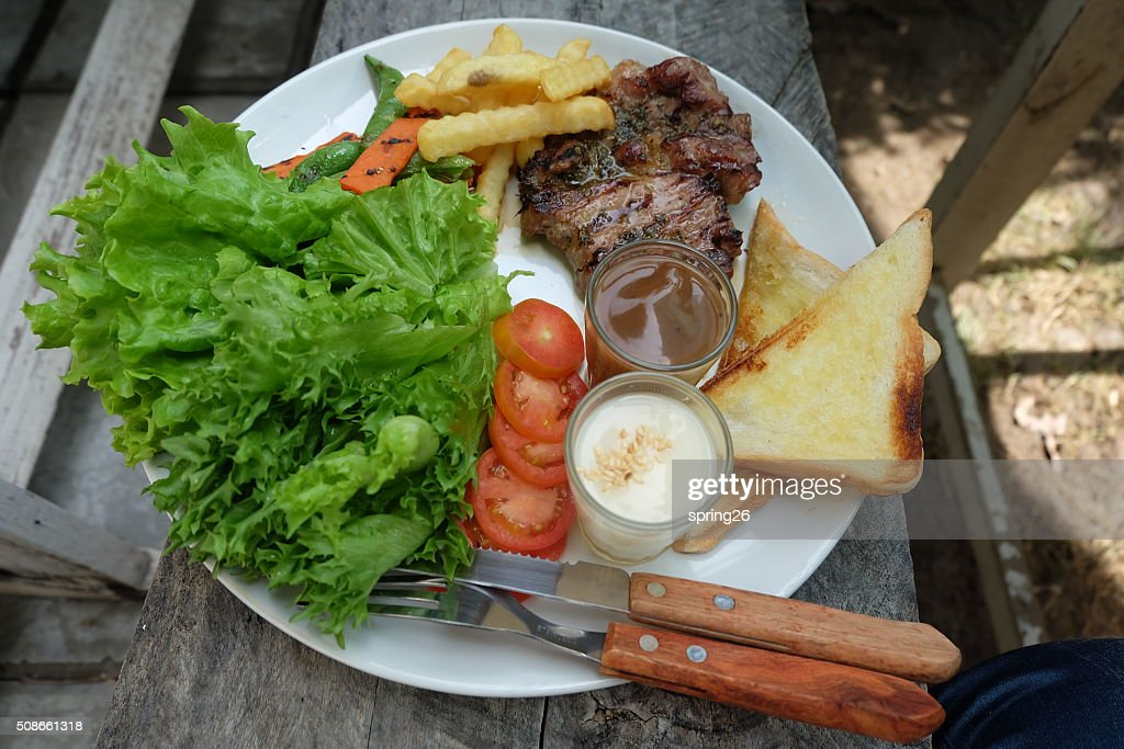 Grilled steak, French fries, bread and vegetables : Stock Photo