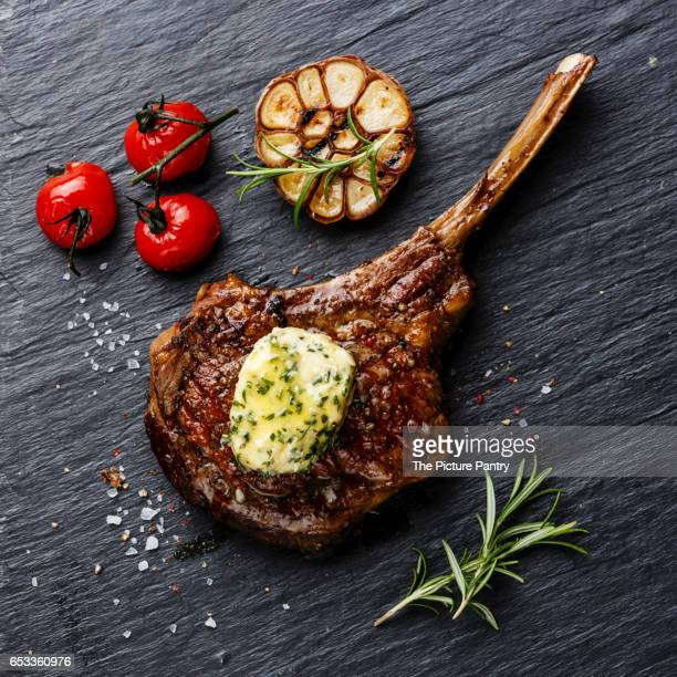 Grilled Steak on bone Veal rib with herb butter on stone slate background