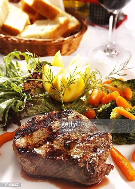 Grilled steak plated with vegetables with bread and wine