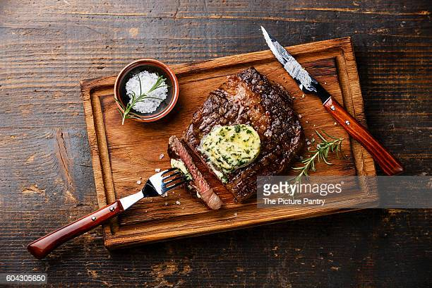 Grilled steak Ribeye with herb butter on cutting board on wooden background