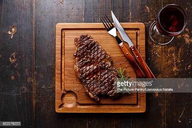 Grilled Steak Striploin and red wine on cutting board on dark wooden background