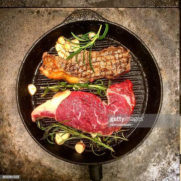 Grilled steaks with rosemary and garlic in a frying pan