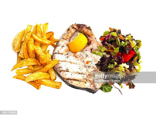 Grilled Swordfish Served With French Fries And Salad On White Background