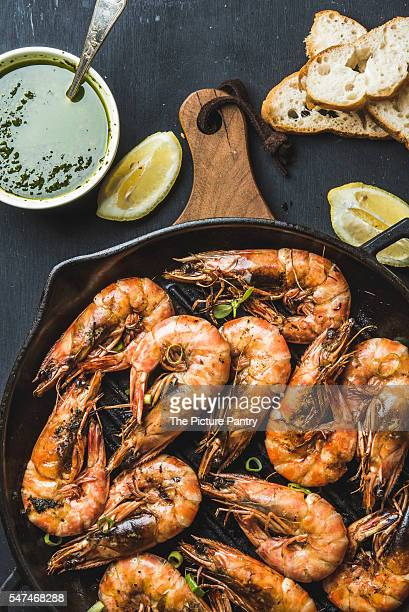 Grilled tiger prawns in dark grilling iron pan on wooden board served with bread, lemon slices and pesto sauce