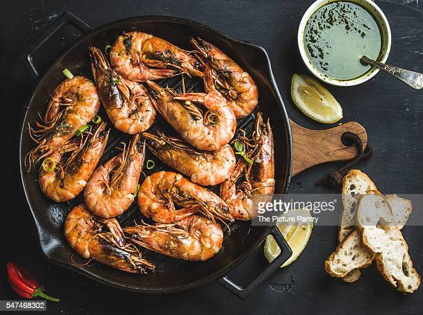 Grilled tiger prawns in dark grilling iron pan on wooden board served with bread, lemon slices, pepper and pesto sauce. Dark background
