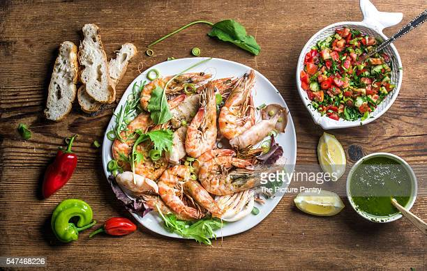 Grilled tiger prawns in white plate served with bread, green salad, lemon slices, peppers and pesto sauce on wooden background