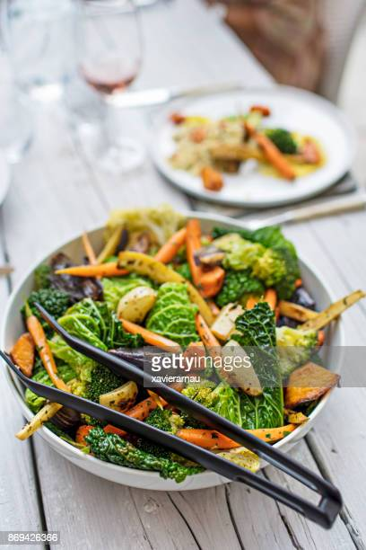 grilled vegetable salad in bowl on dining table - tongs work tool stock photos and pictures
