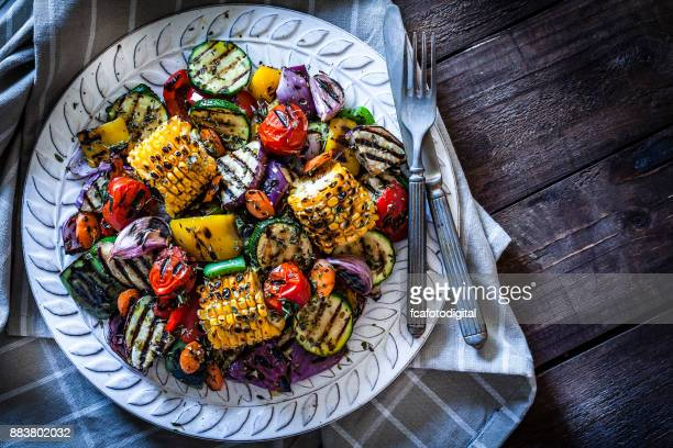 grilled vegetables plate shot from above on rustic wooden table - grilling stock pictures, royalty-free photos & images