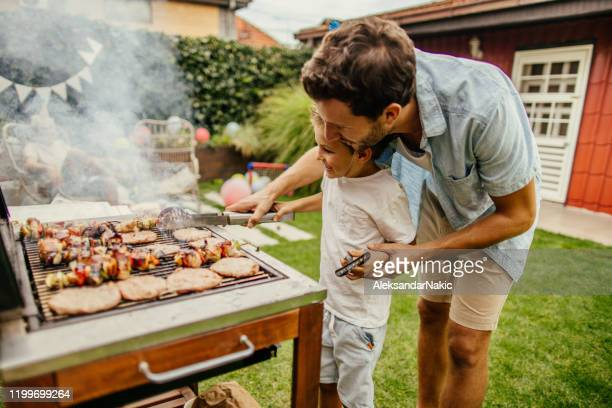 grilling meat with my dad - summer stock pictures, royalty-free photos & images