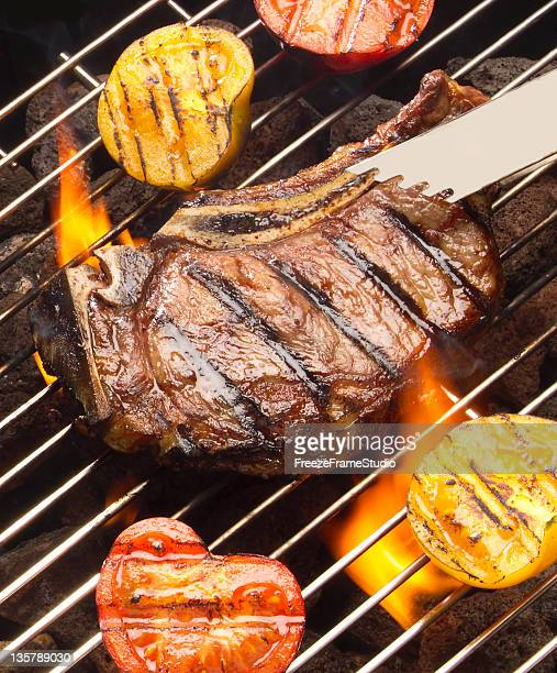 grilling sirloin steak and fresh vegetables with charcoal flames - tongs work tool stock photos and pictures