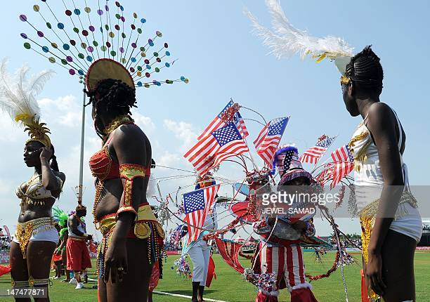 Grils from a local carnival band walk on the field to perform during the first T20 match between West Indies and New Zealand at the Central Broward...