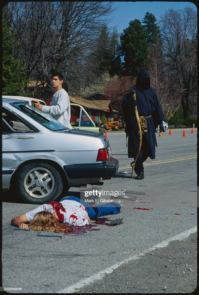 Grim Reaper and Victims at Simulated Accident : Stock Photo