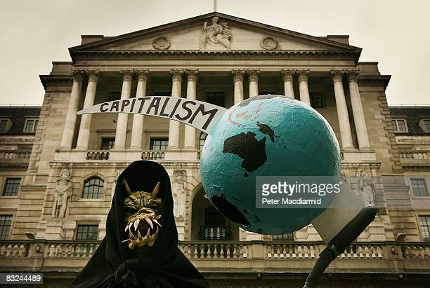 A grim reaper figure holds a globe pierced by the scythe of capitalism in front of the Bank of England during a protest on October 13 2008 in London...