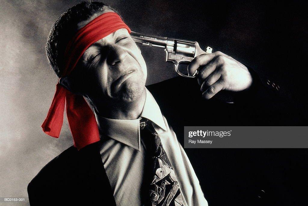 Grimacing businessman pointing gun at his head (tinted B&W) : Stock Photo