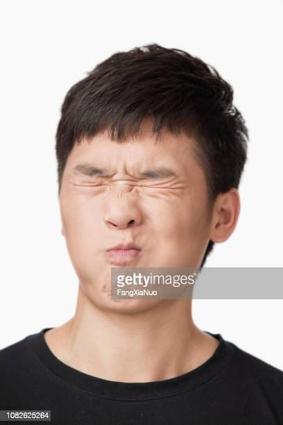grimacing chinese man - sour taste stock pictures, royalty-free photos & images